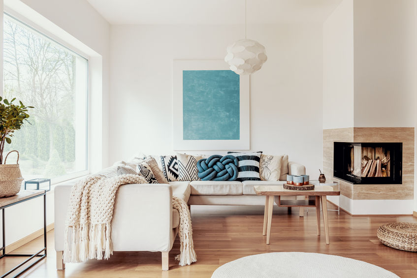 Turquoise Blue Knot Pillow On A Beige Corner Sofa And An Abstract Poster On A White Wall In A Modern Living Room Interior